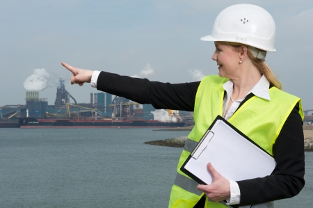 Portrait of a female inspector in hardhat and safety vest pointing finger at industrial site photo