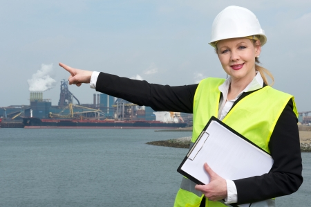 Portrait of a female supervisor in hardhat and safety vest pointing finger to industrial site outdoors photo