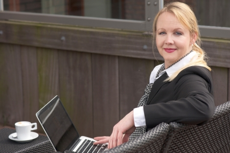 Portrait of a business woman relaxing with laptop and cup of coffee outdoors photo