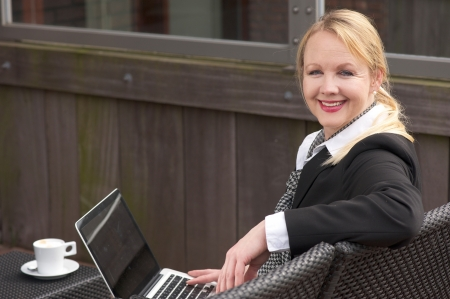 Portrait of a happy business woman working with laptop and relaxing with a cup of coffee outdoors photo