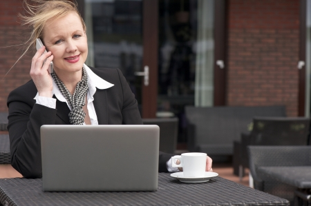 Portrait of a businesswoman on phone outdoors with laptop and cup of coffee photo