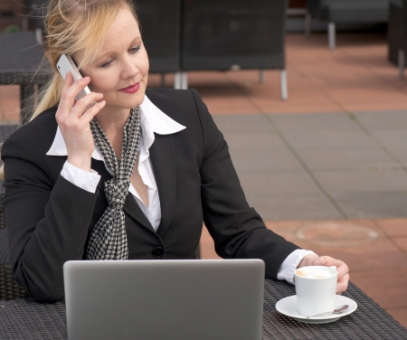 Portrait of a businesswoman on a mobile phone sitting outdoors with laptop and cup of coffee photo