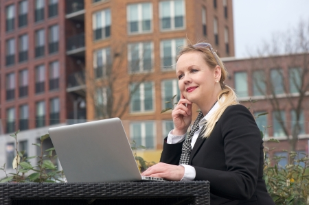 Portrait of a modern business woman sitting with laptop outdoors photo