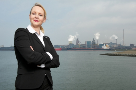 Portrait of a businesswoman standing outside polluted industrial site photo