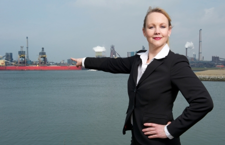 Portrait of a confident business woman pointing finger at ships in the harbor photo