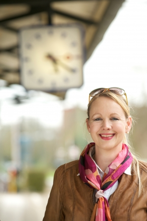 Portrait of a beautiful mature woman smiling under train station clock photo