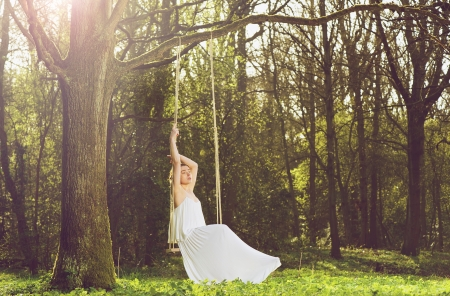 Romantic portrait of a beautiful young bride sitting alone on swing outdoors photo