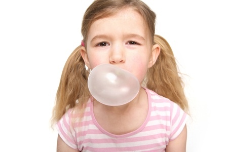 gums: Portrait of a cute little girl blowing a bubble from chewing gum Stock Photo