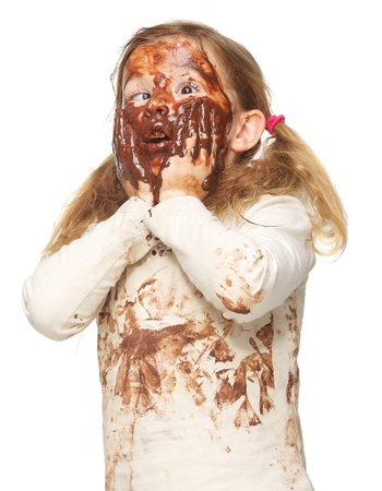 face covered: Portrait of a funny little girl with dirty face covered in chocolate isolated on white