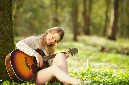 Portrait of a beautiful young woman playing acoustic guitar outdoors photo