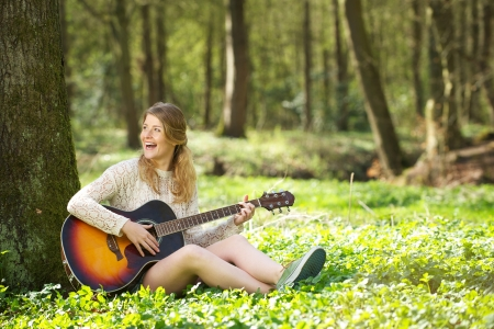 Portrait of a beautiful young woman smiling and playing guitar in the forest photo