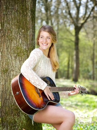 Portrait of a happy young woman smiling with guitar outdoors photo