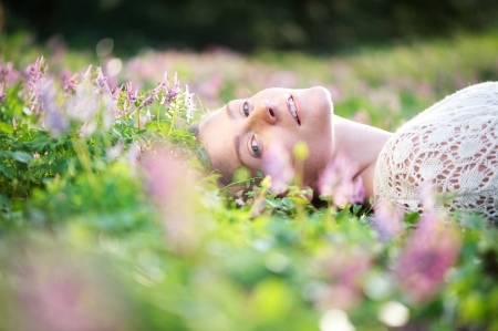 Portrait of a beautiful young woman lying on grass with spring flowers photo