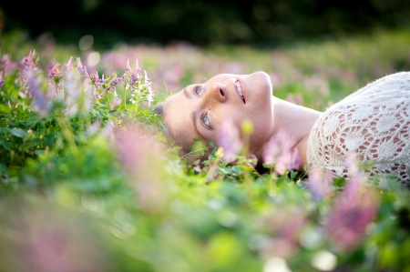 shallow depth of field: Portrait of a beautiful young woman lying in meadow of flowers Stock Photo