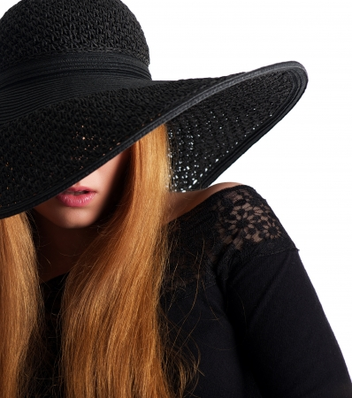 Closeup portrait of a fashion model in black hat isolated on white  photo