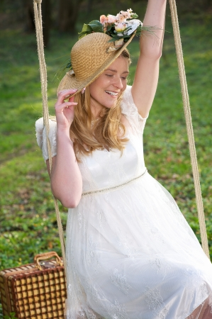 Portrait of a happy woman with hat sitting on a swing outdoors photo