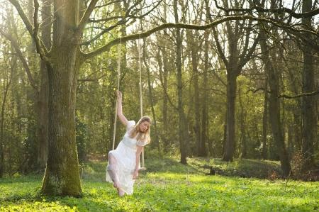 girl on swing: Portrait of a beautiful bride in white wedding dress sitting on swing outdoors