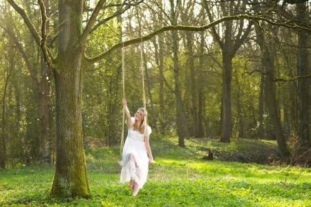 Portrait of a happy bride in white wedding dress sitting on a swing in the woods  photo