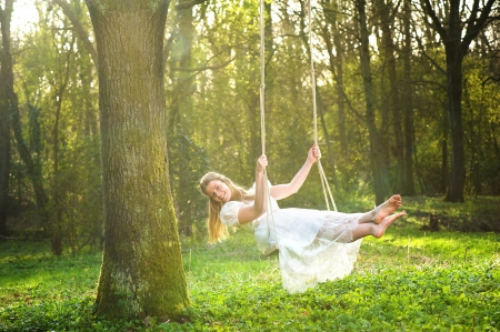columpio: Retrato de una hermosa novia en traje de novia blanco sonriendo y balanceándose en el bosque Foto de archivo