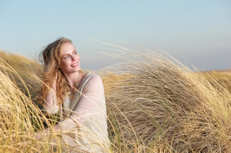 Portrait of a beautiful young woman smiling in the dunes photo