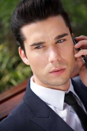 man face close up: Close up portrait of a handsome young businessman on phone outdoors