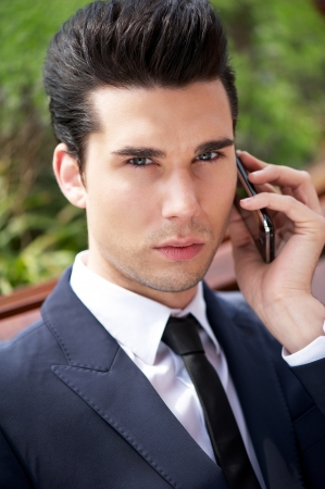serious guy: Close up portrait of a young businessman talking on the phone outside the office Stock Photo