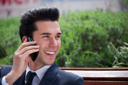 Close up portrait of a happy businessman talking on the phone outside the office photo