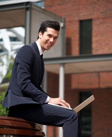Portrait of a handsome young businessman smiling outdoors with laptop photo