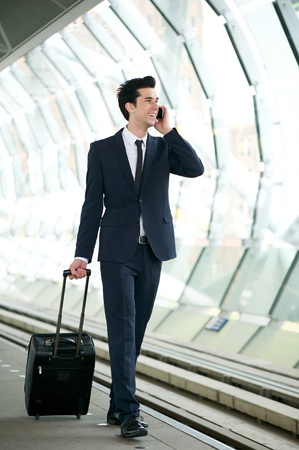 Portrait of a handsome businessman walking on train station platform and talking on the phone