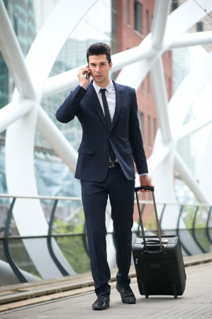 Portrait of a young businessman calling on phone and traveling with bag at metro station photo