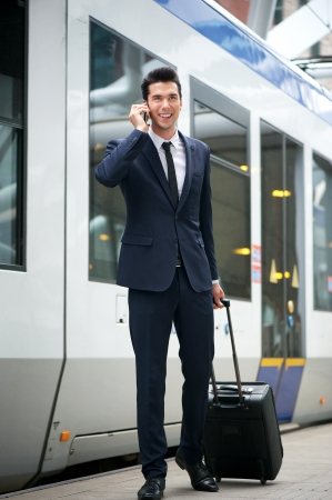 Traveling businessman talking on the phone at metro station with train in background photo