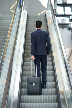 Business man going up escalator holding travel bag - rear view