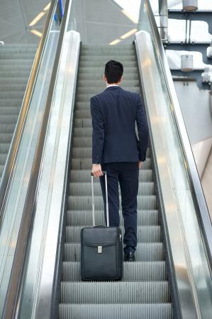 Homme d'affaires allant jusqu'à escalator sac de voyage détention - Vue arrière