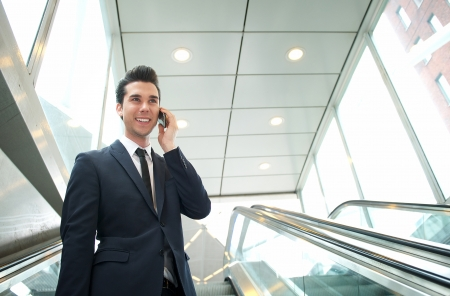 Close up portrait of a happy businessman talking on the phone on escalator photo