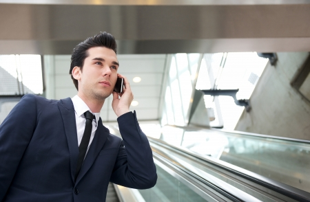 subway station: Portrait of a traveling businessman talking on the phone on escalator