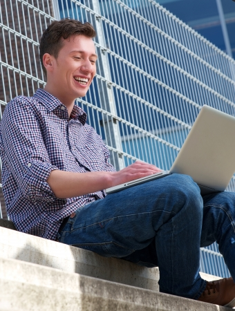 Portrait of a young man smiling at laptop outdoors photo