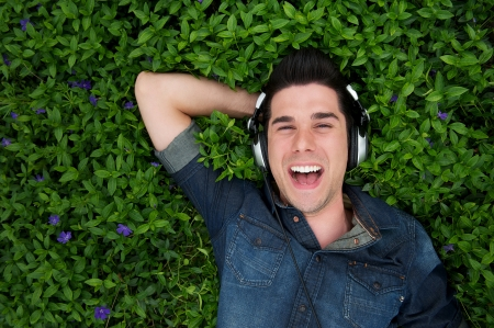top angle: Portrait of a smiling handsome man with headphones outdoors