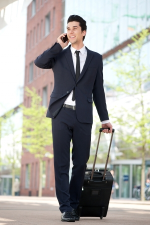 Portrait of a traveling businessman talking on mobile phone photo