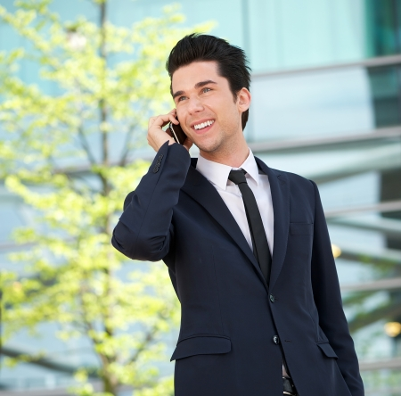 Close up portrait of a handsome businessman talking on mobile phone outdoors photo