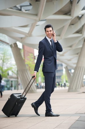 Portrait of a businessman traveling with phone and bag photo