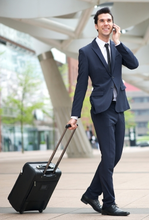 Portrait of a young businessman traveling with phone and bag photo