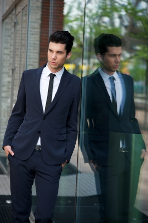 Portrait of a handsome businessman leaning against glass building photo