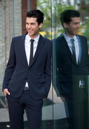 edificio cristal: Retrato de un feliz hombre de negocios apoyado en edificio de cristal