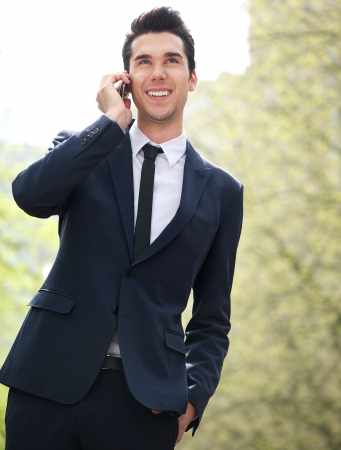 Portrait of a confident young businessman talking on mobile phone outdoors photo