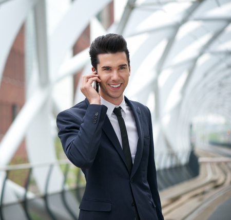 Portrait of a young businessman smiling and talking on the phone at station photo