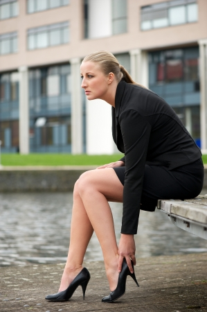 business woman legs: Portrait of a business woman sitting outside and adjust her shoe