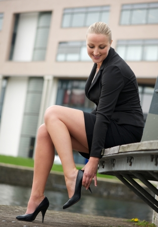 skirt up: Portrait of a young business woman adjust her shoes outdoors Stock Photo