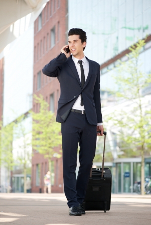 Portrait of a young businessman traveling with bag and mobile phone photo
