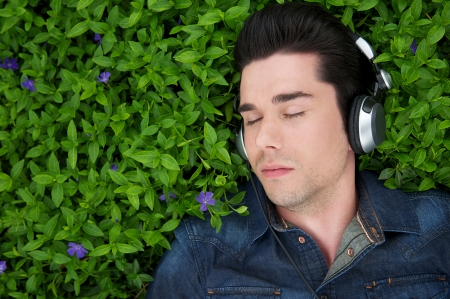 Close up portrait of a young man lying on grass with headphones and eyes closed photo