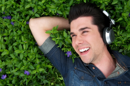 Portrait of a young man lying on grass smiling with headphones photo